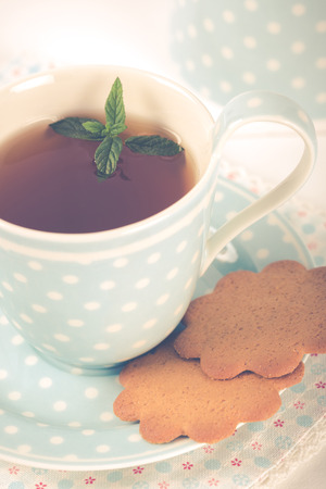 tea and biscuits: Tea with mint cookies served in a porcelain cup and saucer