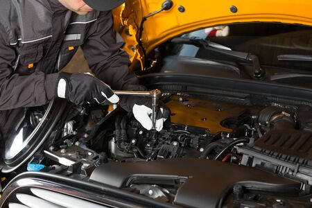 Auto Mechanic performing maintenance on the engine Stock Photo