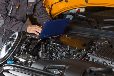 job engine: Car mechanic with a tablet making a diagnosis engine