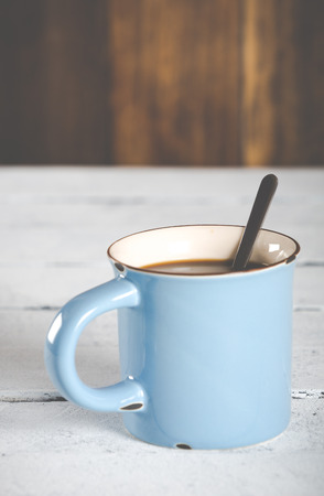 antique table: Cup of coffee in a blue vintage antique table Stock Photo