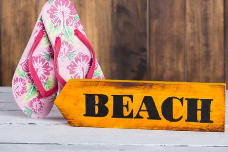 Señal de dirección con la playa hecha a mano y pintado