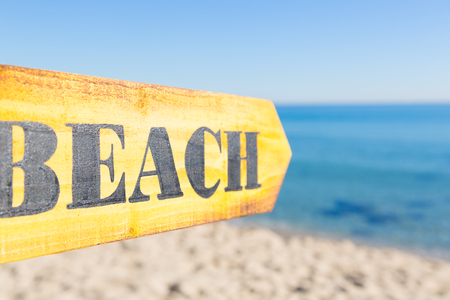 beach access: Wooden sign pointing to a beach on a sunny day