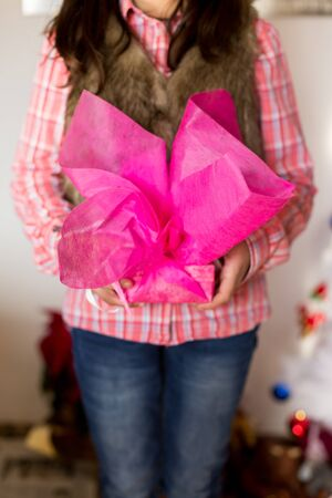 lass: Girl presenting a gift wrapped in brown paper