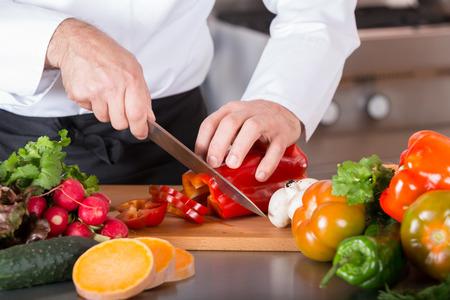Chef schneiden frisches und leckeres Gemüse zum Kochen