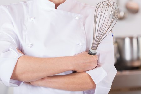 prideful: Chef in the kitchen with his arms crossed and with a whisk Stock Photo