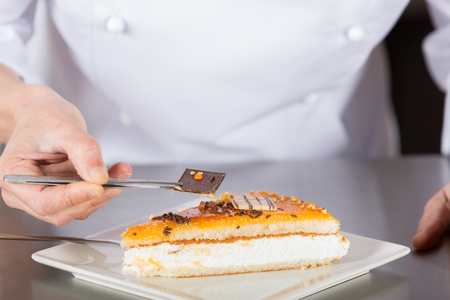 pastry chef: Pastry chef decorating cake yolk and cream Stock Photo