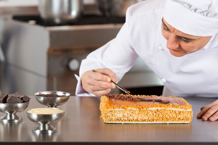 coif: Pastry chef decorating cake yolk and cream Stock Photo