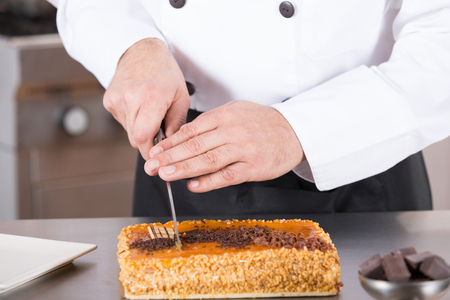 coif: Pastry chef cutting a cake yolk and cream