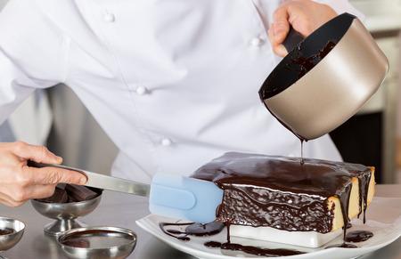 초콜릿 케이크를 장식하는 부엌에서 과자 요리사 스톡 콘텐츠