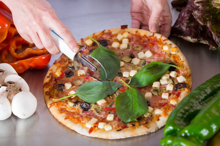 galley: Cook cutting a Mediterranean pizza with vegetables and cheese