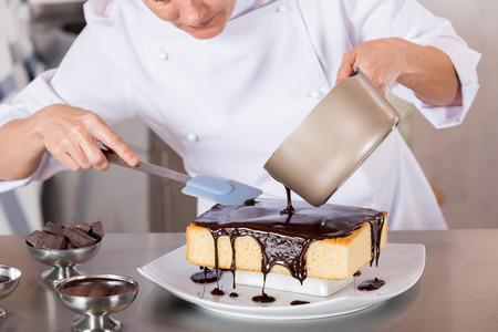 Gebakje chef-kok in de keuken decoreren een taart van chocolade Stockfoto