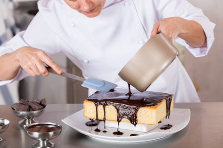 uniform clothing: Pastry chef in the kitchen decorating a cake of chocolate