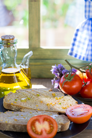 countrified: Bread with tomato and oil by a window