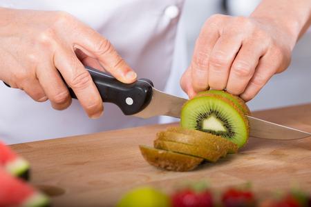 acido: Chef de corte en un ácido kiwi deliciosa Foto de archivo
