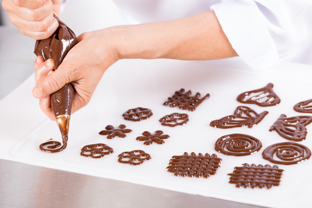 decorate: Chef making figures with chocolate to decorate a cake Stock Photo