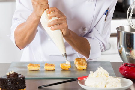 butterfat: Chef decorating with a pastry bag with cream