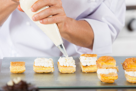 pastry bag: Chef decorating with a pastry bag with cream