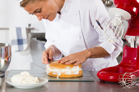 butterfat: Chef decorating a delicious cake with cream
