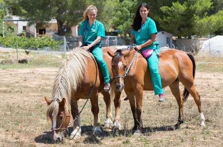 sickly: Two young veterinary mounted on horseback at the farm Stock Photo