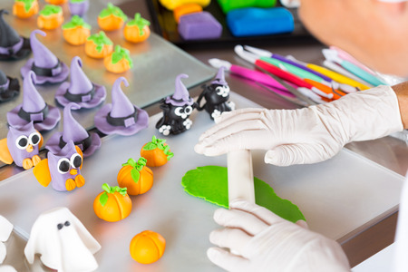 pinzas: Confitero trabajando en las figuras de pasta de Halloween con fondant