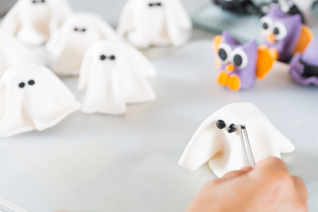 gum paste: Confectioner working on the figures of Halloween with fondant paste