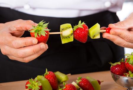 brochetas de frutas: Chef preparando una variedad de brochetas de frutas mixtas