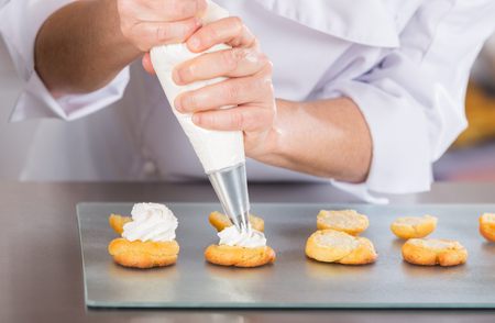 Pastry chef finishing a delicious cream profiteroles