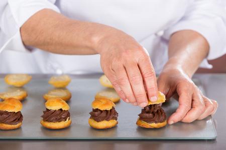 Chef confectioner finishing some delicious chocolate profiteroles photo