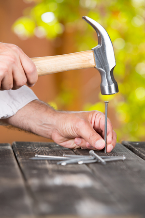 Carpenter nailing a nail in the home garden Stock Photo