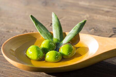 Olives in a spoon over extra virgin olive oil Reklamní fotografie
