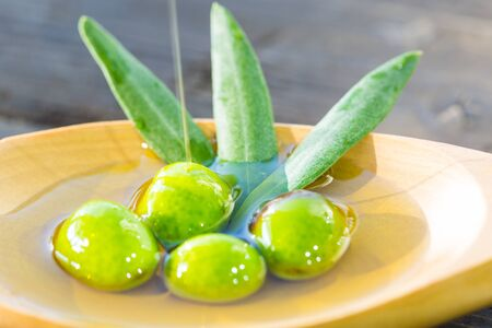 Olives in a spoon over extra virgin olive oil Stock Photo