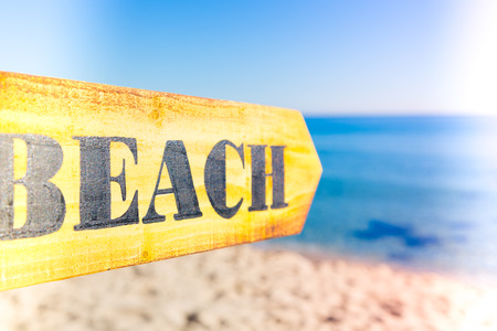Wooden sign pointing to a beach on a sunny day