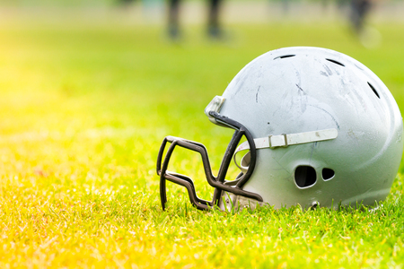 American football helmet on the field grass Stock Photo