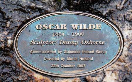 Dublin, Ireland August 17, 2018: Sculpture of writer Oscar Wilde in Merrion Square. The artwork by Danny Osborne was unveiled in 1997. The art shows Wilde reclining on a large boulder. Editorial