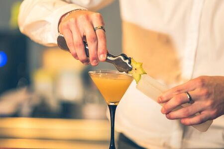 Barman preparing a cocktail from the shaker