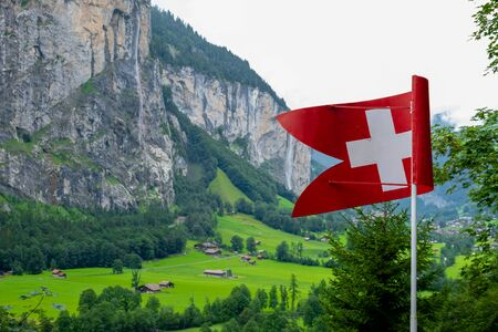 Swiss flag and in the background its typical mountains Фото со стока