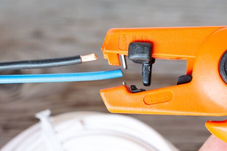 Electrician stripping wires with a machine