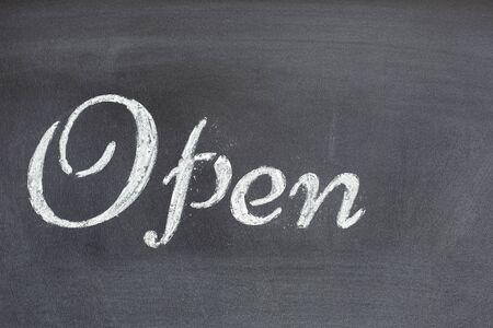 Black chalkboard with the written word Open
