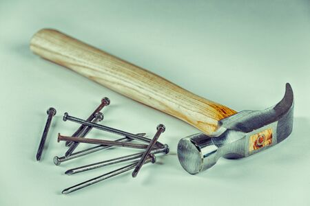 Construction hammer with nails and white background