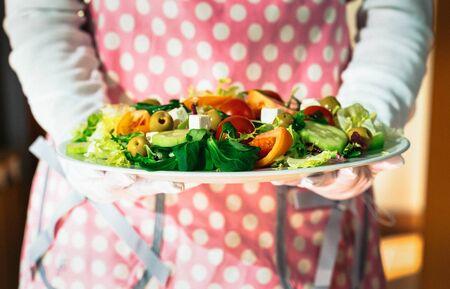Girl presenting a delicious fresh Mediterranean salad Standard-Bild