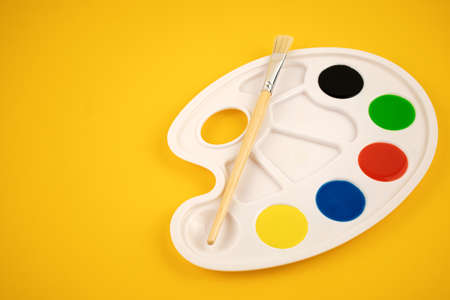 PALETTE OF WATER COLORS WITH A BRUSH ON A YELLOW BACKGROUND. FINE ARTS