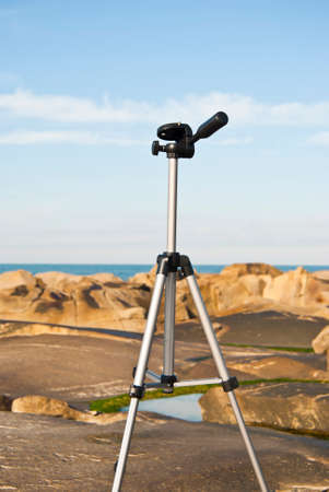 tripod mounted: Tripod mounted on a stone on the beach