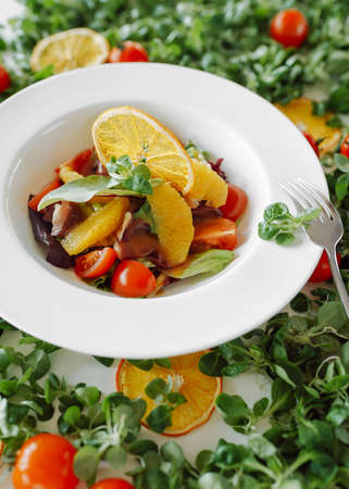 salad in oranges, tomatoes and bacon over green background