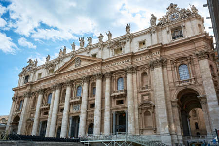 View of the facade of St. Peter's Basilica at Saint Peter's Square in the Vatican City in Rome, Italy, under blue cloudy sky on a spring day.