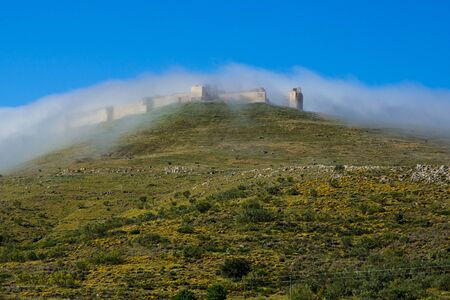 Ancient ruins of the citadel in Reina covered by fog. Extremadura. Spain.