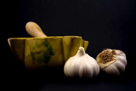 Displays a ceramic mortar with pestle and garlic.  photo