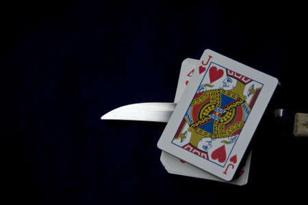 Displays a deck of cards pierced by a knife