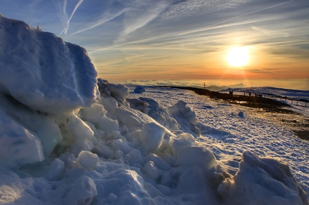Awesome sunset with beautiful colors over mountainous snowy landscape photo