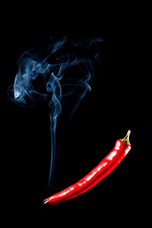 Smoking red chilli pepper with charred tip isolated on black photo