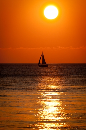 A silhouetted boat gently sails against a warm and peacefull sunset photo